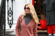 Claudia Schiffer is seen on the school run in a furry salmon coloured jumper, she grabs a starbucks and has a helping hand to stay dry under a big black umbrella.