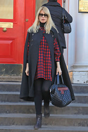 Claudia stays warm and chic in a black wool cape coat.