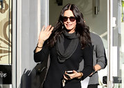 Courteney Cox jazzed up a plain black sweater with a charcoal scarf looped around her neck.