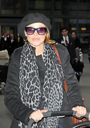 Dannii piled on the accessories at Heathrow airport. Purple tinted sunglasses, a black beret, and a leopard scarf complete the look.