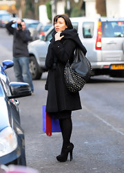 Sporting a studded leather bag, Dannii Minogue made a fashionably chic appearance while out an about. The studded bag brought instant style to her layered tench coat.