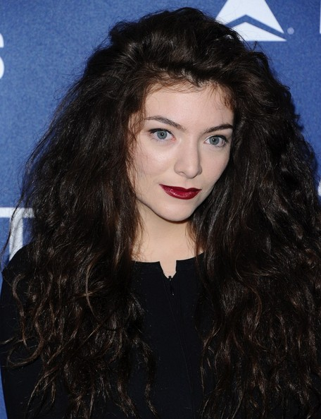 Lorde gave her dark look a splash of color with a sweep of red lipstick.