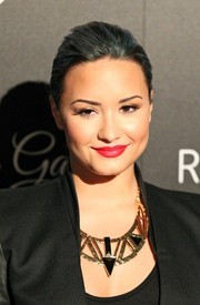 Demi Lovato brightened up her black look with a geometric gold necklace.