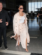 Demi Lovato traveled in diva-chic style wearing a blush-colored silk trenchcoat by Elizabeth and James.