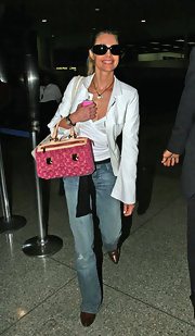 Denise Richards carried a bright pink canvas shoulder bag while traveling through LAX airport.