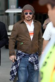 Johnny Depp wears a rustic brown leather jacket for this interesting bad boy ensemble.