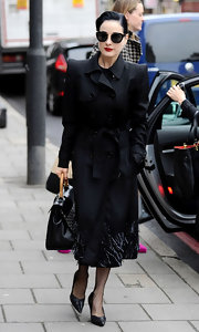 Dita Von Teese's trenchcoat has a beaded hem and structured shoulders.