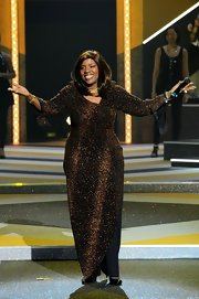 Gloria Gaynor glittered on stage at the Etam fashion show in this gold and black evening dress.