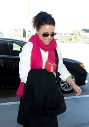 Julia Louis-Dreyfus added some color to her black-and-white outfit with a bright red scarf during a flight out of LAX.