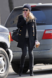 Kirsten looks classically stylish in this dark wool pea coat with charming gold buttons. The smoking, however, is not so darling.