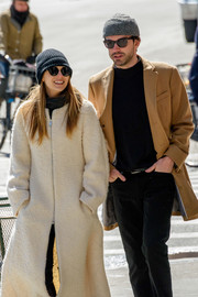 Elizabeth Olsen was spotted out in New York City looking warm in a black knit beanie and a white coat.