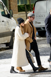 Elizabeth Olsen took a stroll in New York City wearing black knee-high boots and a white coat.
