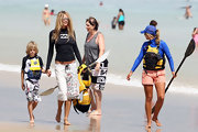 Elle MacPherson strides along the beach with her son in tow while wearing multi-patterned board shorts.