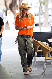 Elle MacPherson was casual chic in an orange blouse, cargo pants and black flip flops.