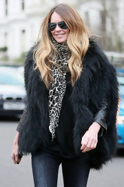 Elle dons a giraffe print scarf with aviators and fur coat while out in London.
