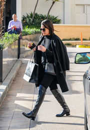 Lea Michele looked toasty in a black wool coat layered over a turtleneck while shopping at Barneys.