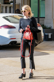 Emma Roberts accessorized with a red Balenciaga cross-body tote for a pop of color to her dark outfit.