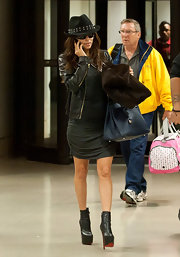 Eva Longoria traveled in style in a draped jersey dress topped off with black leather ankle platform boots.