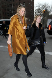 Molly Sims offset her mustard coat with black satin platforms and matching opaque tights.