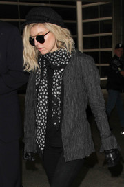 Fergie jazzed up her dark airport outfit with a star-print scarf by Saint Laurent.