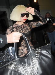 Lady Gaga dresses to impress - here wearing a black lace outfit and dramatic shield sunglasses with gold detail.