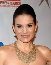 Kara DioGuardi accented her bare neckline with a bronzed statement necklace.