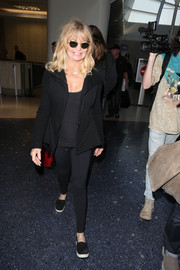 Goldie Hawn stayed comfy in a black zip-up jacket and matching leggings while catching a flight.