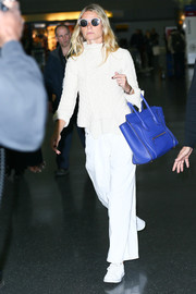 Gwyneth Paltrow finished off her comfy airport attire with white leather sneakers by Adidas x Raf Simons.