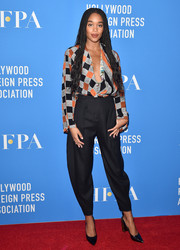 Laura Harrier kept it relaxed yet stylish in a harlequin-print blouse by Louis Vuitton at the HFPA Grants Banquet.