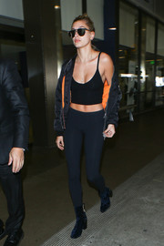 Hailey Baldwin paraded her cleavage and abs at LAX in a low-cut black crop-top by Are You Am I.