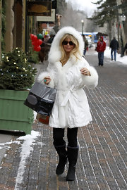 Goldie Hawn bundled up from head to toe in a furry coat and black sheepskin boots.