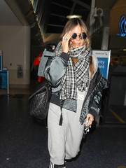 Heidi Klum layered a plaid scarf over a bomber jacket and a sweater dress for her toasty airport look.