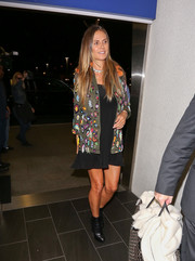Heidi Klum caught a flight out of LAX wearing a beaded military jacket over a little black dress.