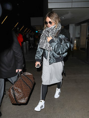 Heidi Klum stayed warm and comfy in a gray sweater dress by Adidas while catching a flight.