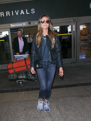 Heidi Klum kept warm with a fringed black leather jacket by Saint Laurent during a flight.