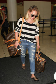 Hilary Duff had her hands full with a Louis Vuitton Monogram Keepall duffle and a Neverfull GM bag.