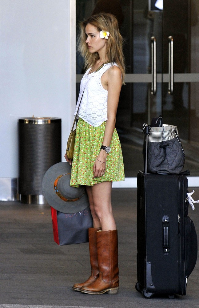 Isabel Lucas looks very thin and wears a flower in her hair as she waits for her car at the valet with her luggage after arriving at Sydney Kingsford-Smith Airport.