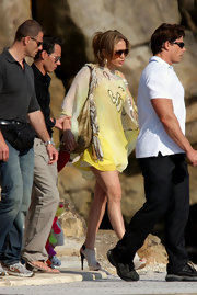 The diva stepped out in a sheer yellow cover up with fierce slingback, peep toe ankle booties.