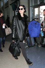 Jaimie Alexander wore black round sunglasses to match her edgy airport outfit.