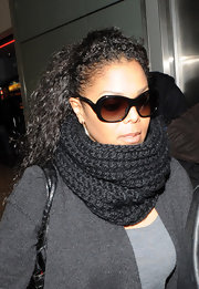 Janet arrives at Heathrow Airport all covered up in a knited black scarf.
