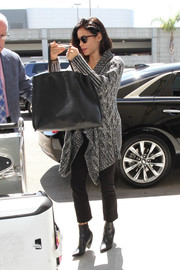 Jenna Dewan-Tatum caught a flight at LAX wearing black bootcut jeans and an oversized cardigan.