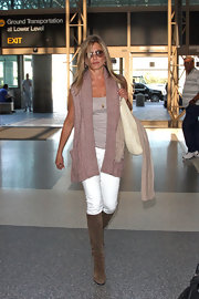 Jen kept comfy while traveling in white jeans paired with an oversized mauve vest sweater.