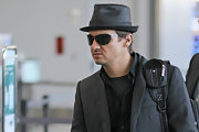 Jeremy Renner travels in style in a fedora hat and matching black shades while arriving at Pearson International airport.