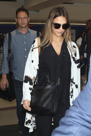 Jessica Alba showed off a chic crocodile cross-body tote by Givenchy while arriving on a flight at LAX.