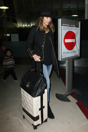 Jessica Alba was spotted at LAX rolling a white LOMS spinner suitcase.