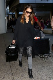 Jessica Alba teamed a black lace-hem shirtdress with gray jeans and boots for a punky airport look.