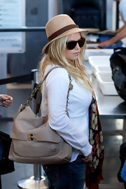 Jessica Simpson looked stylish in her beige fedora while waiting at the airport. Her rich floral scarf and sunglasses added the finishing touches to her cool, casual style.