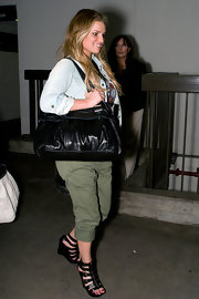 Jessica wore cropped khaki pants with zip-front, gladiator wedges.