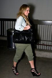 Jessica paired her green cargo pants with a black tote bag, while hitting LAX airport.