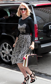 January Jones looked sweet toting a rose in her Prada bag while wearing this patterned dress.